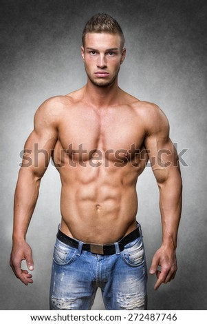 Young man with well trained body, biceps, abs and pecs and wearing a denim trousers - stock photo