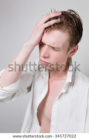 Young man with wet hair in a white shirt. Headache