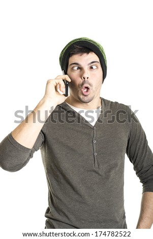 Young man with wool cap and cross eyed talking on phone isolated on a white background - stock photo