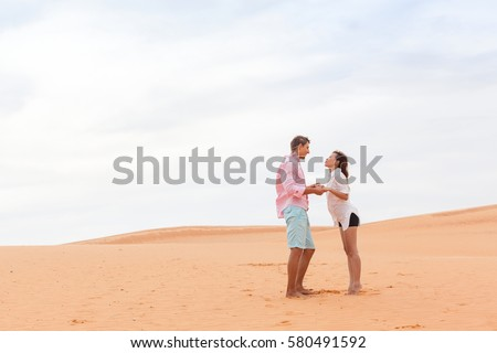 Young Man Woman In Desert Beautiful Couple Asian Girl And Guy Hold Hands Sand Dune Landscape Background