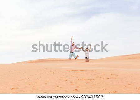 Young Man Woman Jump Up In Desert Beautiful Couple Asian Girl And Guy Sand Dune Landscape Background