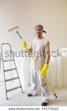 Young man - worker standing with painting roller - stock photo