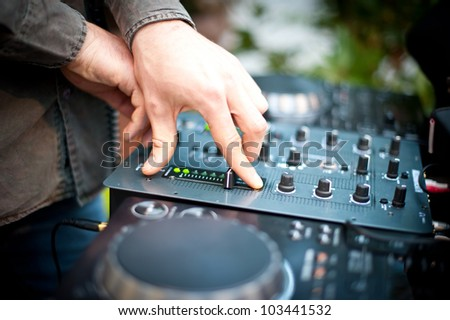 Young man working as dj with mixer. Shallow focus on hands.