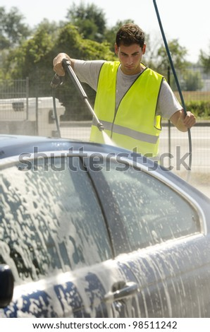 Young man working at car wash station - stock photo