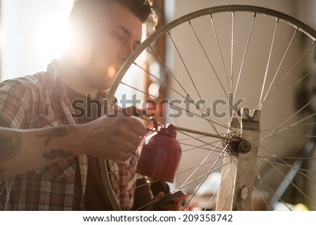 Young man working in a biking repair shop - stock photo