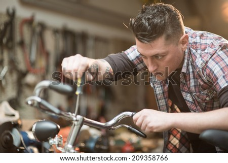Young man working in a biking repair shop