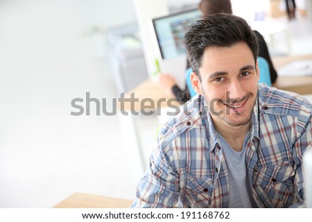 Young man working in office on computer - stock photo
