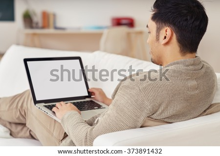 Young man working on a blank laptop with the screen visible to the camera as he reclines on a comfortable sofa at home, rear over the shoulder view - stock photo