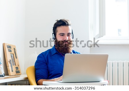 Young Man working on a Computer and listening to Music - stock photo