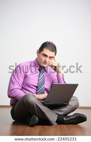 Young man working on a laptop computer from home - stock photo