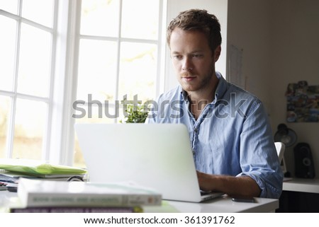 Young man working on laptop computer - stock photo