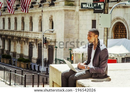 Young man working on street. A young black college student is sitting outside, working on a laptop computer, thinking.  Wall Street sign in the background.  - stock photo