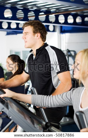 Young man working out with friends in the gym - stock photo