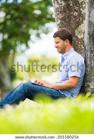 Young man working outside on laptop in park under a tree - stock photo