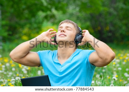 Young man working with a laptop and listening music on headphone outdoors
