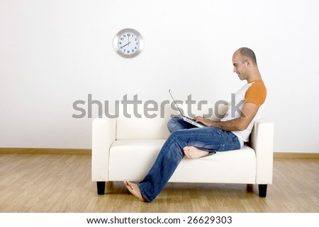 Young man working with a laptop at home - stock photo