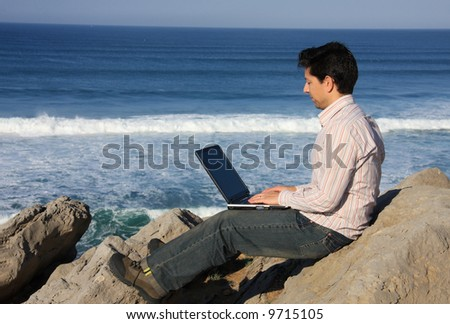 Young man working with a laptop enjoying a beautiful seascape - stock photo