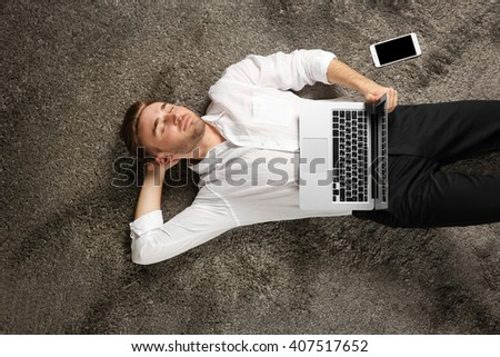 Young man working with a laptop on the floor