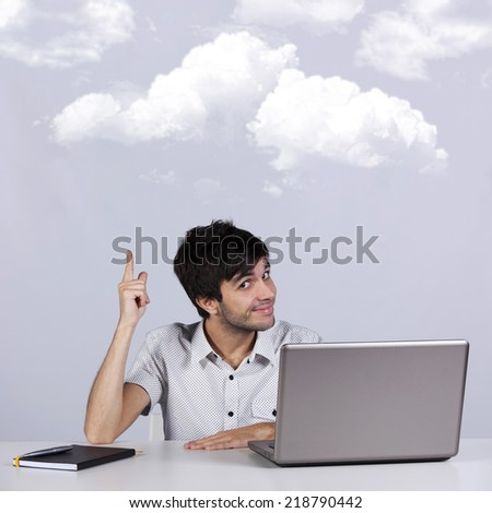 Young man working with his laptop  pointing to the cloud (cloud computing concept)