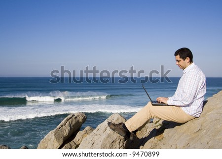 young man working with the laptop at the beach - stock photo