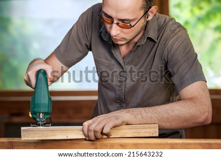 Young man working with wood. Natural background behind - stock photo