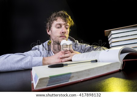 Young man writing in book while studying at table against black