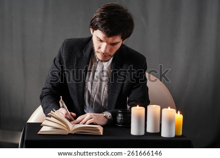 Young man writing notes in the notebook. Coffee, candles and enigmatic atmosphere. - stock photo