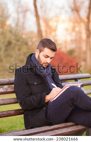 Young man writing on a park bench