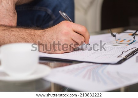 young man writing on paper while sitting. closeup image of hand writing using pen - stock photo