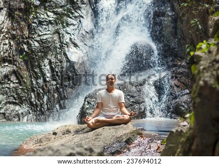 young man yoga engaged in the waterfall in the mountains yoga  - stock photo