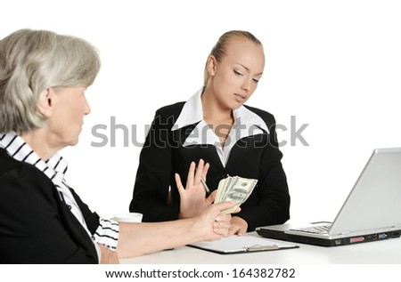 Young manager and her elderly customer have a talk in office