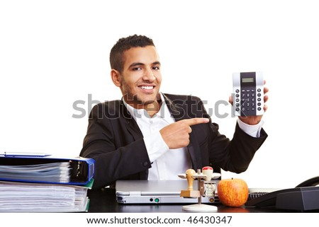 Young manager at his desk showing a calculator