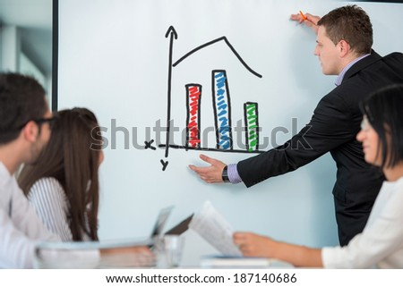 Young manager giving presentation on board to colleagues - stock photo