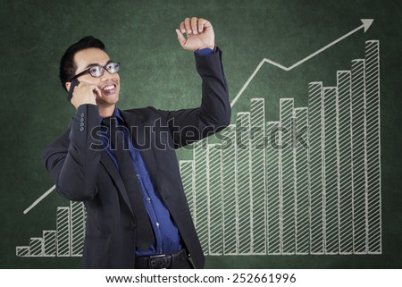 Young manager talking on the phone while expressing success with a background of business growth chart - stock photo