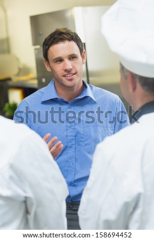 Young manager talking to the staff standing in a kitchen - stock photo
