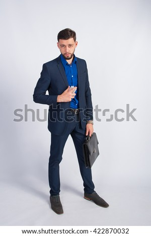 Young manager with a briefcase and phone - stock photo
