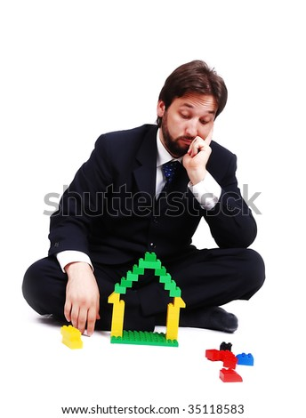 Young mane wearing suit is making a house with cubes toys - stock photo