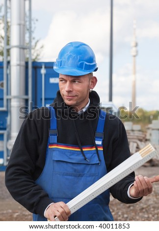Young manual worker in blue hardhat and workwear holds foldable ruler
