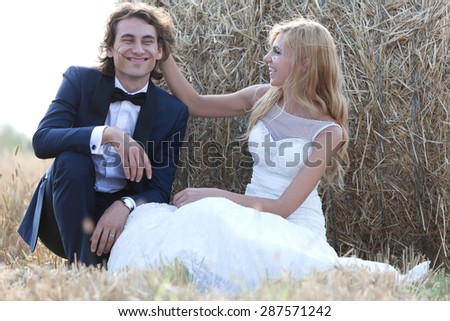Young married couple having fun beside a hay bale. She i?s playing with his hair and he is enjoying it. - stock photo