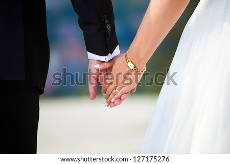 Young married couple holding hands on wedding day - stock photo