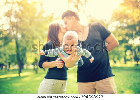Young married couple holding newborn child and kissing. Happy Family, father's and mother's day concept.  - stock photo