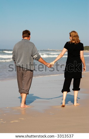 Young married couple in love walking hand-in-hand on the beach during their winter vacation in South Africa. - stock photo