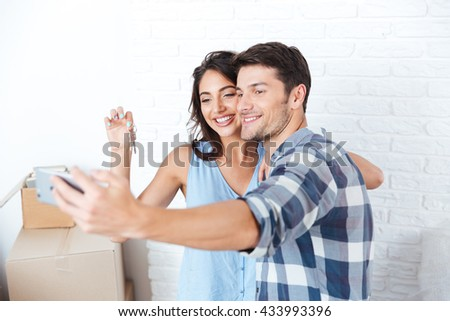 Young married couple making selfie holding keys in new flat - stock photo