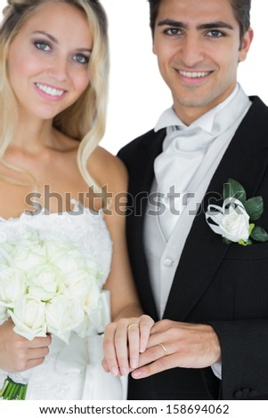 Young married couple posing wearing wedding rings smiling at camera - stock photo