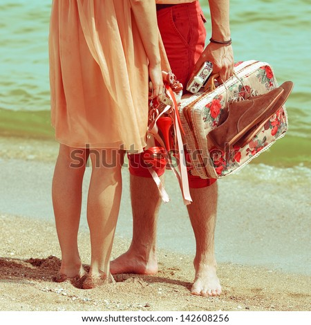 Young married couple standing together on beach holding their photo camera and  shoes. Sunny summer day. Outdoor shot