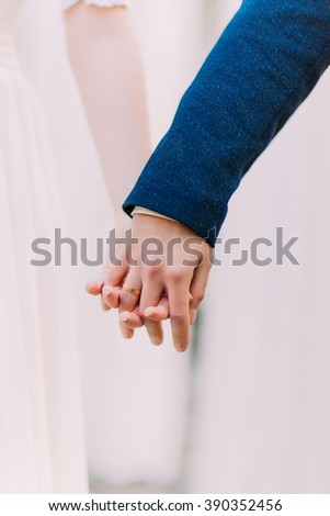 Young married couple tenderly  holding hands at the wedding day close up - stock photo
