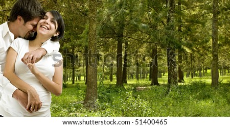young married happy pregnant coupe in a forest - stock photo