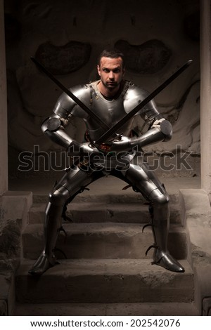 Young masculine man in historical costume. Furious medieval warrior with armor and two swords attacking on steps of ancient temple, dark background - stock photo