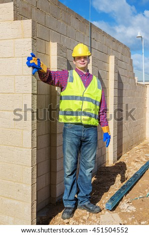 Young mason construction worker on the construction site near  brick  wall - stock photo