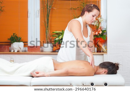 Young massage therapist giving a massage in massage salon. - stock photo